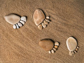Trace feet steps of a pebble stone walking on the sea sand backdrop — Stock Photo