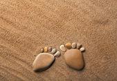 Deux pieds de trace, faites d'une pierre de caillou sur le sable de la mer du désert — Photo