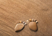 Two trace feet made of a pebble stone on the sea sand desert — Photo