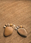 Pair trace feet made of a pebble stone on the sea sand desert texture backdrop — Stock Photo
