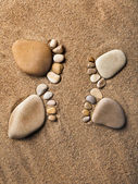Trace bare feet made of pebble stones on the beach sand background — Stock Photo