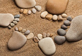 Trace feet of a pebble stone on the sea sand backdrop — Stock Photo