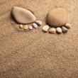 Stock Photo: Two trace feet made of pebble stone on sesand desert