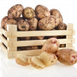 Young potatoes in a wooden box isolated on white - Stock Photo