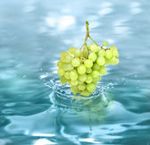 Bunch grape falling in a refreshing drink — Stock Photo