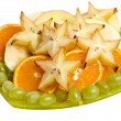 Assorted fruits of carambola, orange, grapes on a glass plate isolated — Stock Photo