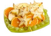 Frutas sortidas de uvas de carambola, laranja, em uma placa de vidro isolado — Foto Stock