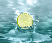 Slice lime falling in a refreshing drink — Stock Photo