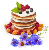 Pancakes stack with fresh berries and honey on white background — Stock Photo