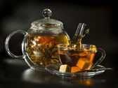 A glass teapot and cup with Flower Chinese tea on a black background — Stock Photo