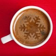 Coffee cup with christmas snow flake on red napkin background - Stock Photo