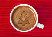 Cup coffee with christmas tree on a red napkin background — Stock Photo