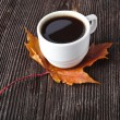 Coffee cup on the autumn fall leaves and wooden surface background — Stock Photo #17183873