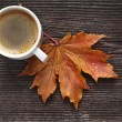 Coffee cup on the autumn fall leaves and wooden surface background — Stock Photo #17183881