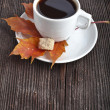 Coffee cup on the autumn fall leaves and wooden surface background — Stock Photo #17183923