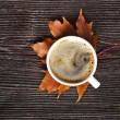 Coffee cup on the autumn fall leaves and wooden surface background — Stock Photo #17183997