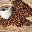 Stock Photo: Coffee cup and jute sack close-up on wooden table
