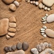 Trace bare feet walking made of pebble stones on the beach sand background — Stock Photo #17184587