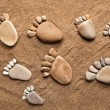 Trace bare feet walking made of pebble stones on the beach sand background — Stock Photo #17184781