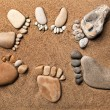 Trace bare feet walking made of pebble stones on the beach sand background — Stock Photo #17184883