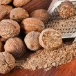 Nutmeg with steel hand grater on wooden background - Photo