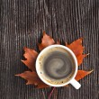 Coffee cup on the autumn fall leaves and wooden surface background — Stock Photo