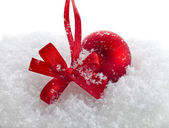Christmas red ball with ribbon bow on snow — Stock Photo