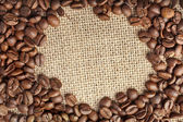 Border frame of dark coffee beans grains on the sackcloth texture background — Stock Photo