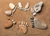 Trace bare feet walking made of pebble stones on the beach sand background — Stockfoto