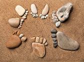 Trace-barfuss wandern hergestellt aus kiesel steine auf dem strand sand-hintergrund — Stockfoto