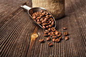 Coffee beans on vintage wooden board and metallic scoop — Stock Photo