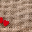 Valentine's day card with two red hearts symbol on canvas sack texture background - Stockfoto