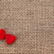 Valentine's day card with two red hearts symbol on canvas sack texture background - Foto Stock