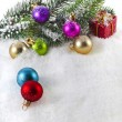 Christmas colorful balls and fir branch on white snow background — Stock Photo #21188819