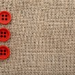 Canvas burlap background texture with red buttons — Stock Photo