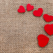 Border frame of red hearts on sack canvas burlap background texture — Stock Photo