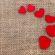 Border frame of red hearts on sack canvas burlap background texture — Stock Photo #21189147