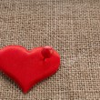 Valentine's day red heart symbol with needle on fabric sack texture background — Stock Photo