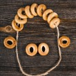 Fun face with curly hair made of bagels old ancient wood texture — Stock Photo