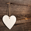 Love heart hanging on wooden texture background, valentines day card concept - Stock Photo