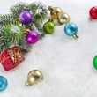 Christmas colorful balls and fir branch on white snow background — Stock Photo #21189485