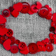 Royalty-Free Stock Photo: Border frame of red buttons and hearts on sack canvas burlap background texture