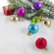 Christmas colorful balls and fir branch on white snow background — Stock Photo #21189669