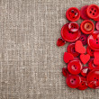 Border of red buttons and hearts on canvas burlap background texture — Stock Photo #21189703