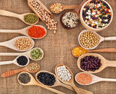 Various grain, beans, legumes, peas, lentils in spoon on the sackcloth background — Stock fotografie