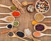 Verschiedene getreide, bohnen, hülsenfrüchte, erbsen, linsen in löffel auf den sack-hintergrund — Stockfoto