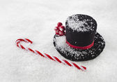 Black top hat snowman with Cane on white snow background — Stock Photo