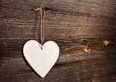 Láska srdce visí na dřevěné textury pozadí, valentýn karty koncept — Stock fotografie