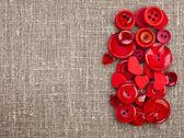 граница красные кнопки и сердца на холсте мешковины фоновой текстуры — Стоковое фото