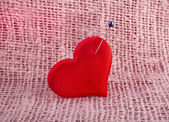 Valentine's day red heart symbol with needle on pink fabric sack texture background — Stock Photo